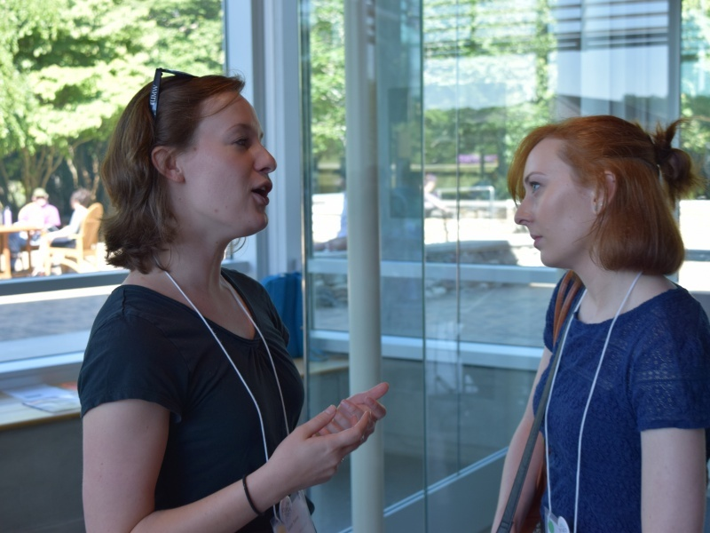 Leah Tams (left), COPLAC Digital Program Associate, speaks with instructional technologist during morning break on Saturday, June 11 in Rhoades Robinson Hall.