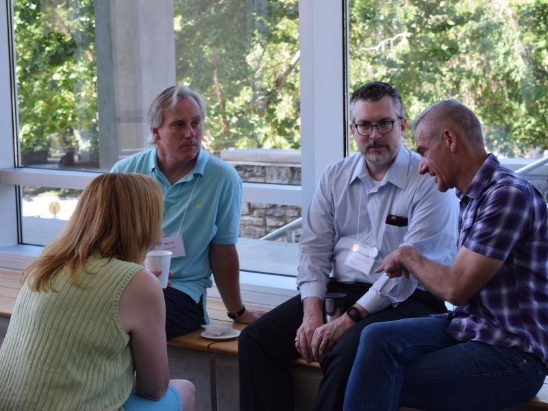 Ellen Pearson (green shirt) and Jeff McClurken (grey shirt), COPLAC Digital Co-Principal Investigators, meet with faculty pair at morning break on Saturday, June 11 in Rhoades Robinson Hall.